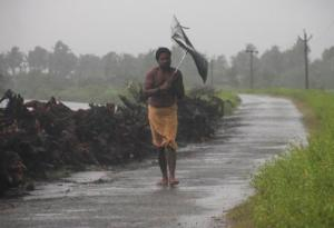 A man struggles with an umbrella in strong winds and rain caused by Cyclone Hudhud in Gopalpur in Ganjam district in the eastern Indian state of Odisha October 12, 2014. Cyclone Hudhud blasted India's eastern seaboard on Sunday with gusts of up to 195 km per hour (over 120 mph), uprooting trees, damaging buildings and killing at least five people despite a major evacuation effort. REUTERS/Stringer (INDIA - Tags: DISASTER ENVIRONMENT)